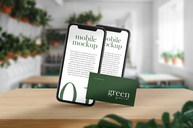 Clean minimal business card and mobile mockup on wood table in green cafe with and light shadow.