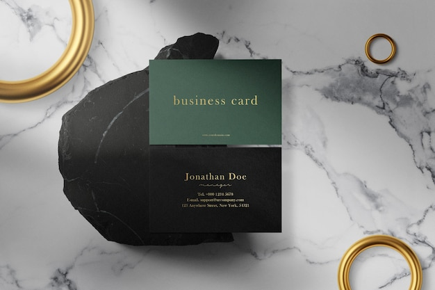 Clean minimal business card mock up on black stone with rings