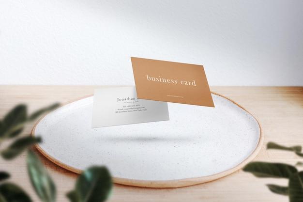 Pulisci il biglietto da visita minimo finto che galleggia su un piatto da pranzo con foglie