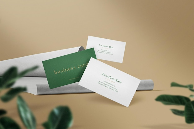 Clean minimal business card mock up floating on paper fold with leaves