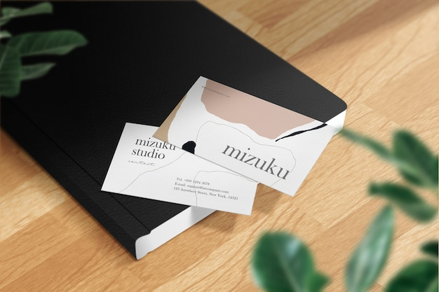 Clean minimal business card mockup on black book leather and leaves.