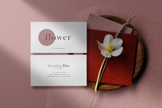 Clean minimal business card mockup on color background with flower plate. psd file.