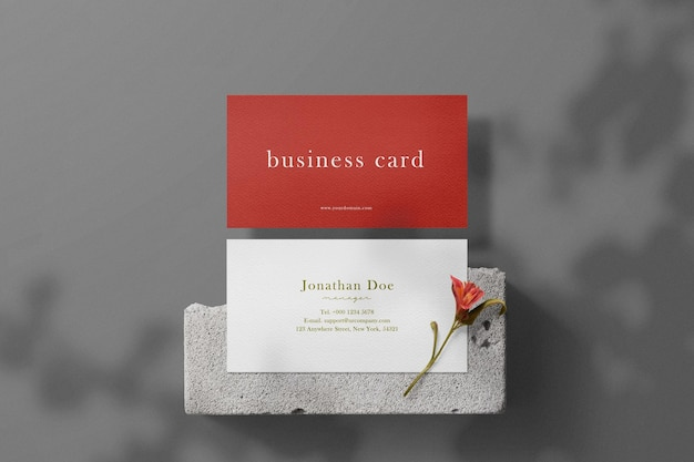 Clean minimal business card mockup on concrete with flower