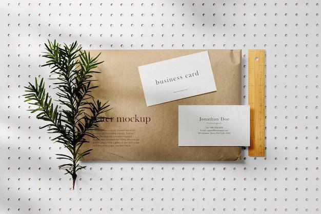 Pulisci il modello di biglietto da visita minimo su busta con foglie
