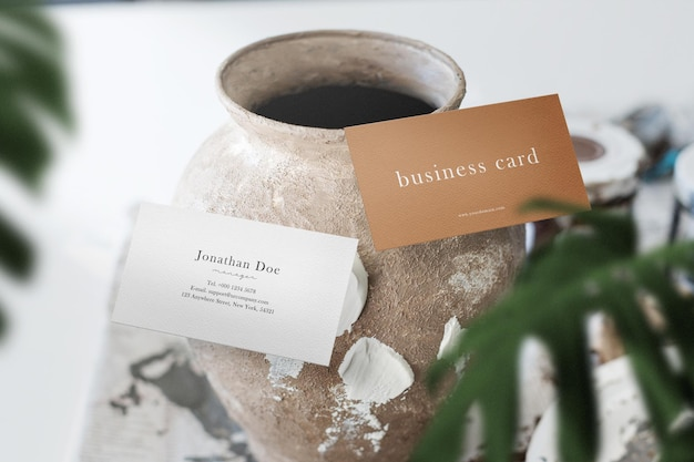 Clean minimal business card mockup floating on clay jar with leaves
