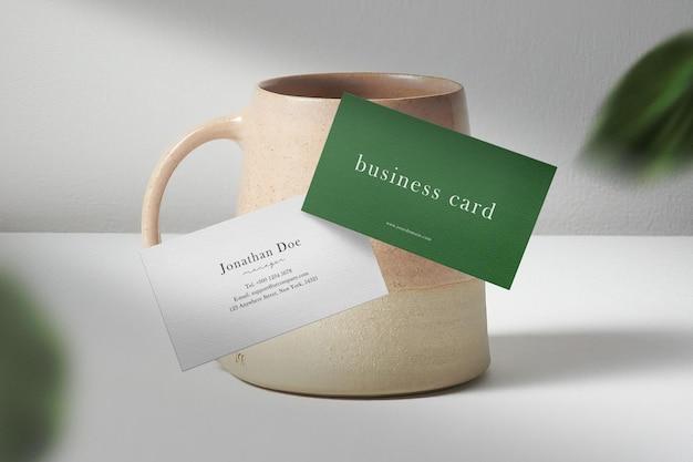 Чистый минимальный макет визитки, плавающий на чайной чашке с листом