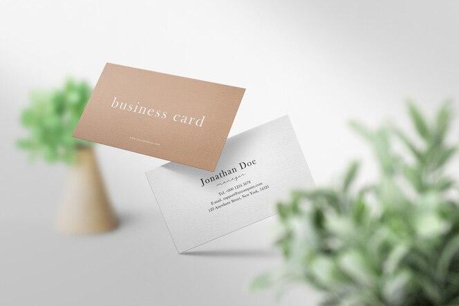 Чистый минимальный макет визитки, плавающий на полу с зелеными листьями