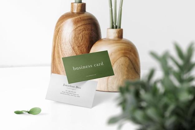 木製の花瓶と葉でトップテーブルに浮かぶ最小限の名刺モックアップをきれいにする