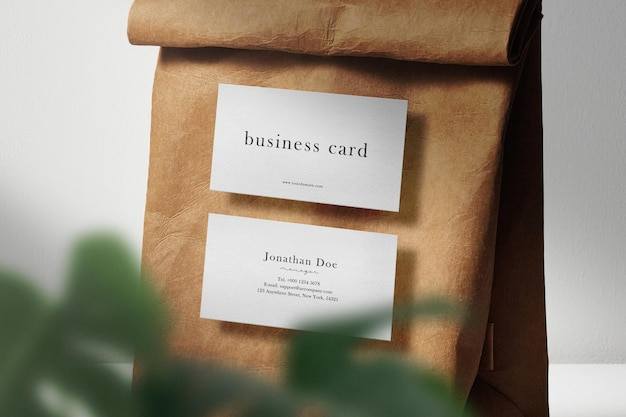 Clean minimal business card mockup floating on paper bag with leaves