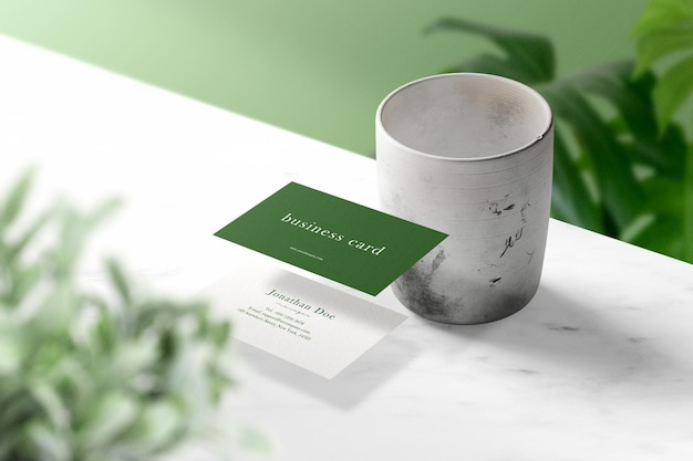 Pulisci il modello di biglietto da visita minimo che galleggia sul marmo superiore con foglie e vaso