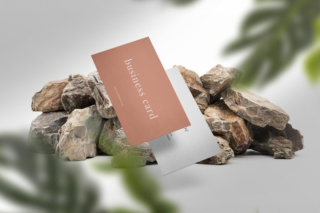 Clean minimal business card mockup floating on top stones with leaves