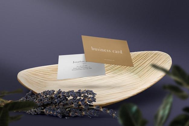 Pulisci il modello minimo del biglietto da visita che galleggia su un piatto di legno con il fiore.