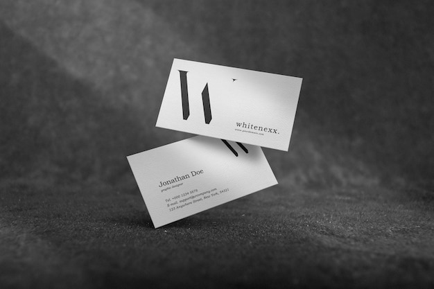 Clean minimal business card mockup on a gray carpet with light and shadow background. psd file.