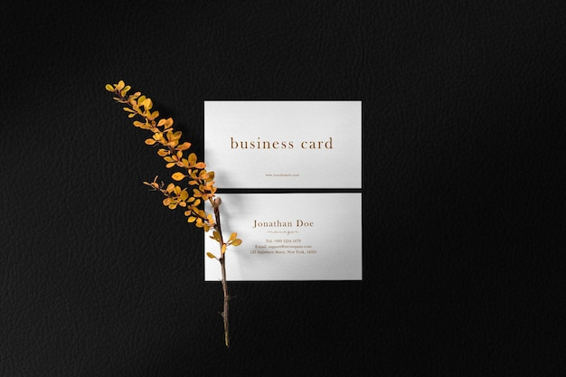 Clean minimal business card mockup on leather surface with yellow plant.