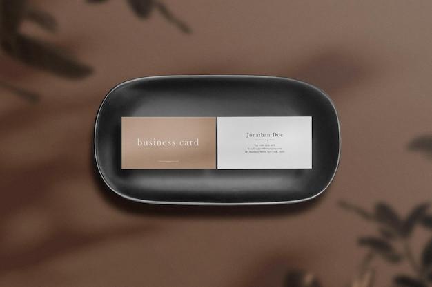 Чистый минимальный макет визитки на черной тарелке с листьями