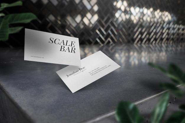 잎이있는 콘크리트 테이블에 최소한의 명함 모형을 청소하십시오.