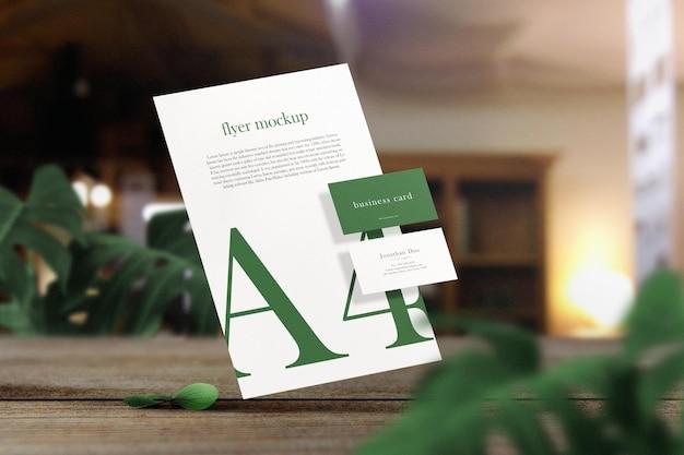 葉のある木製の上に浮かぶ紙a4の最小限の名刺モックアップをきれいにする