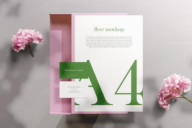 ドキュメントボックスとピンクの花で紙a4の最小限の名刺モックアップをきれいにする