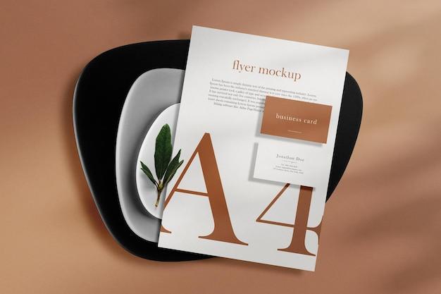プレートと葉の背景で紙a4の最小限の名刺モックアップをきれいにします。 psdファイル。 Premium Psd