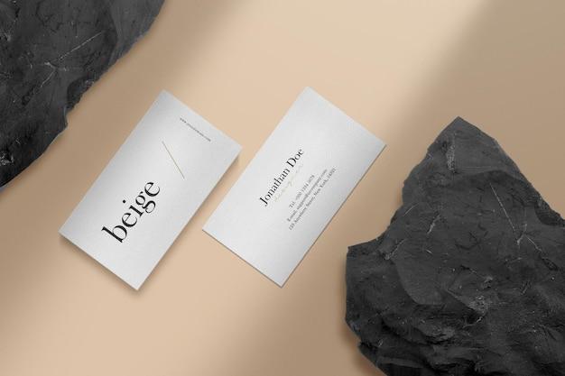 黒い石の背景で床に最小限の名刺のモックアップをきれいにします。
