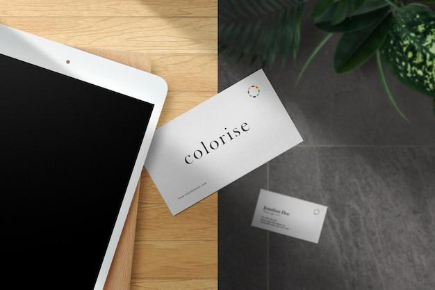 タブレットの背景を持つトップテーブルの最小限の名刺のモックアップをきれいにします。 psdファイル。
