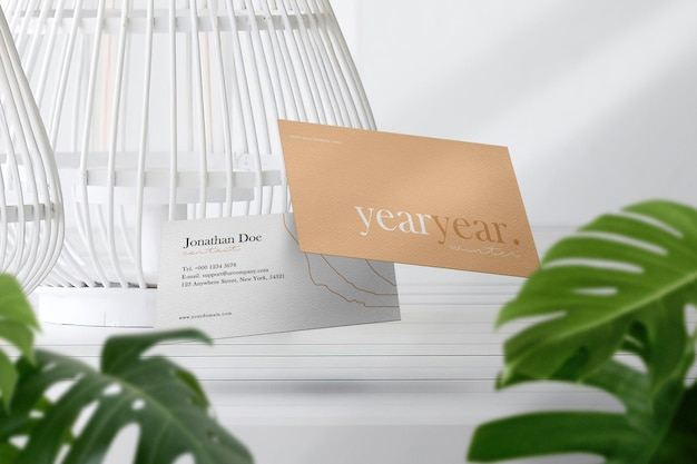 잎이있는 상단 흰색 테이블에 깨끗한 최소한의 명함 모형