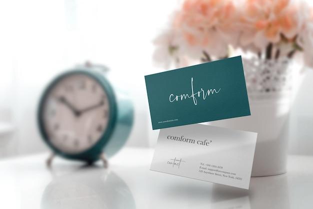 Чистый минимальный макет визитки на белом столе с часами и вазой с цветами