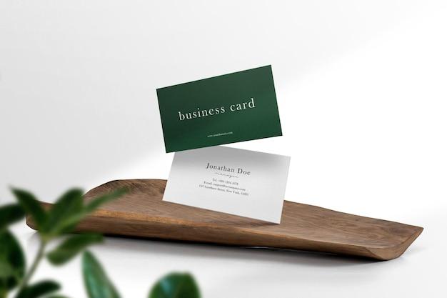 Чистый минимальный макет визитной карточки на деревянных и листьях.