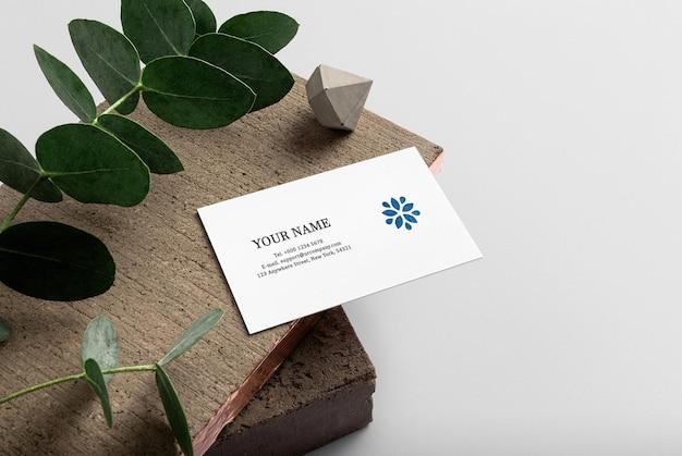 葉で木の板に最小限の名刺のモックアップをきれいにする