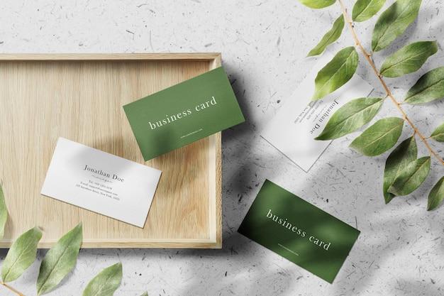 Чистый минимальный макет визитки на деревянной тарелке с листьями