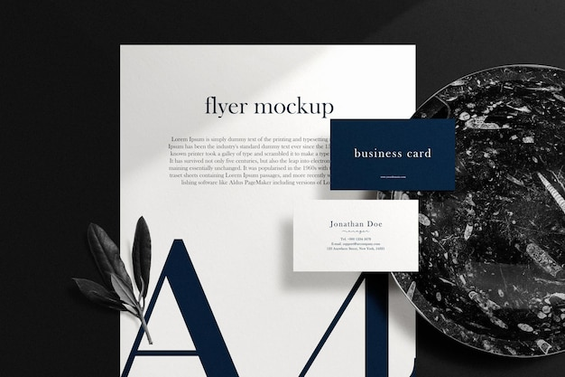 Clean minimal business card mockup on paper a4 with black marble plate and leaves