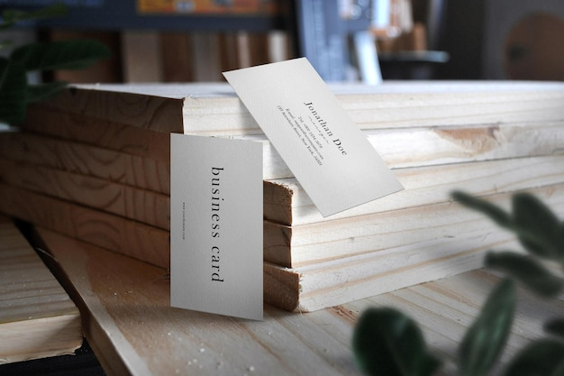 Clean minimal business card mockup on plank with leaves