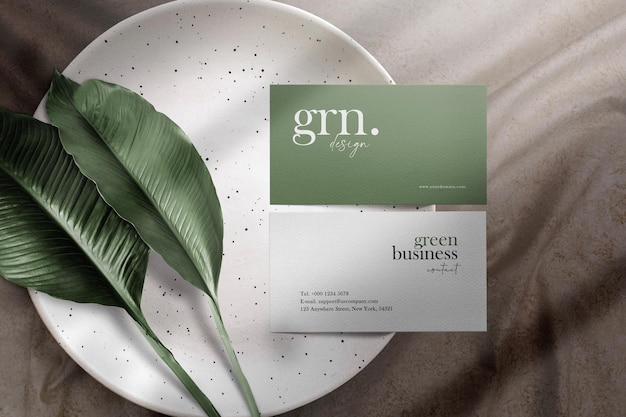 Clean minimal business card mockup on plate with leaves and fabric background
