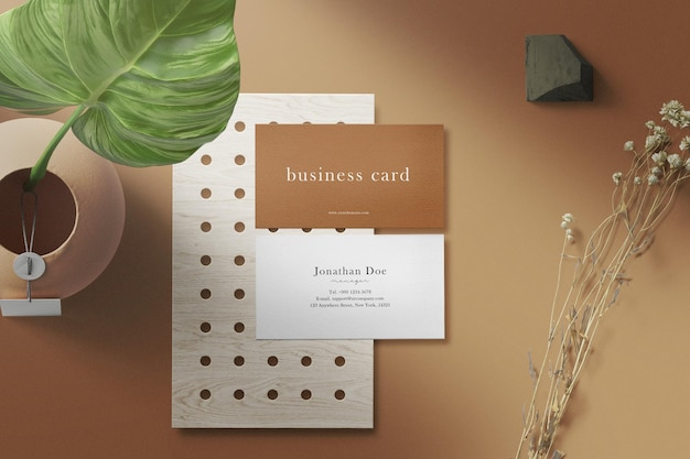 Clean minimal business card mockup on plate with vase flower and dry plant