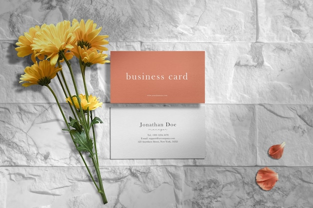 Clean minimal business card mockup on split face stone with flowers