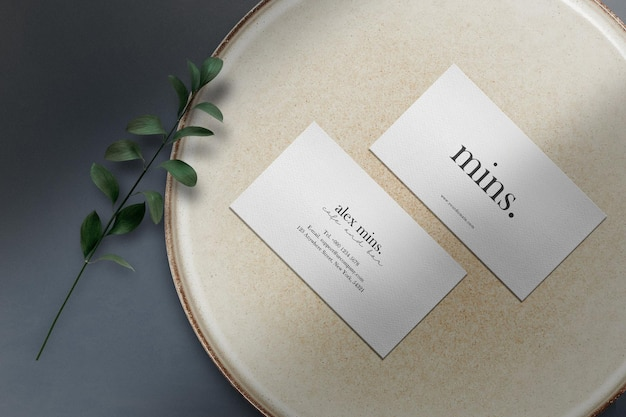 Clean minimal business card mockup on stone plate with green leaves