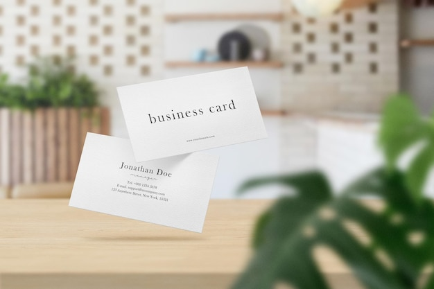 Clean minimal business card mockup on top table in soft cafe with leaves