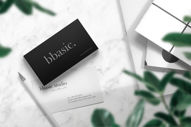Clean minimal business card mockup on white marble with books and pen