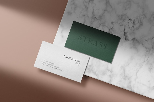 Clean minimal business card mockup on white marble with shadow background. psd file.