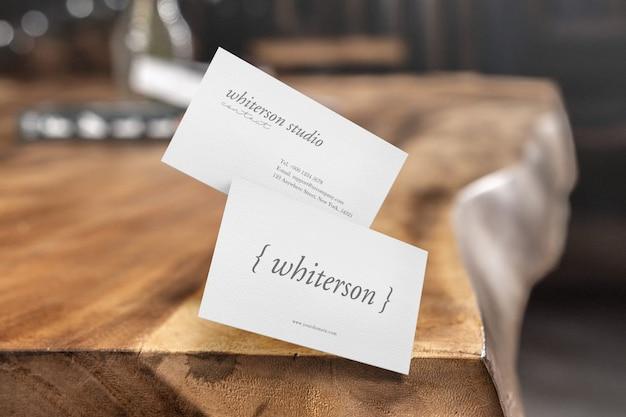 Clean minimal business card mockup on wood corner background.