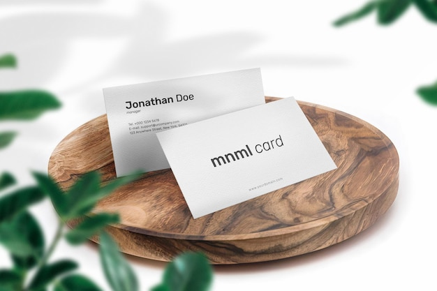 Clean minimal business card mockup on wood plate with leaves and shadow