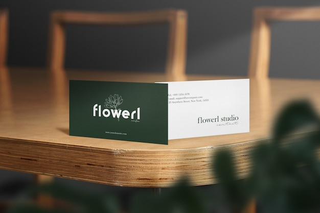 Clean minimal business card mockup on wood table with the light and leaves shadow.