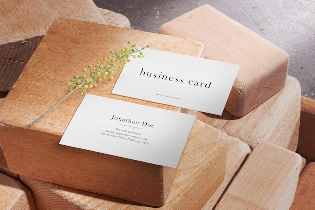 Clean minimal business card mockup on wooden blocks with plant