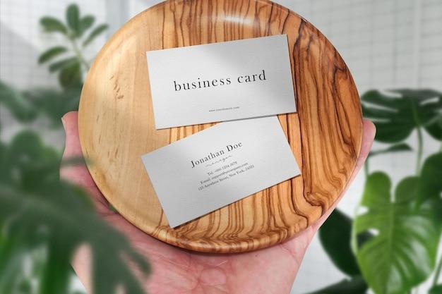 Pulisci il modello minimo del biglietto da visita sul piatto di legno che tiene in mano e foglie.