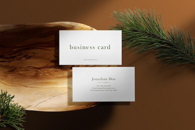 Clean minimal business card mockup on wooden plate with conifer