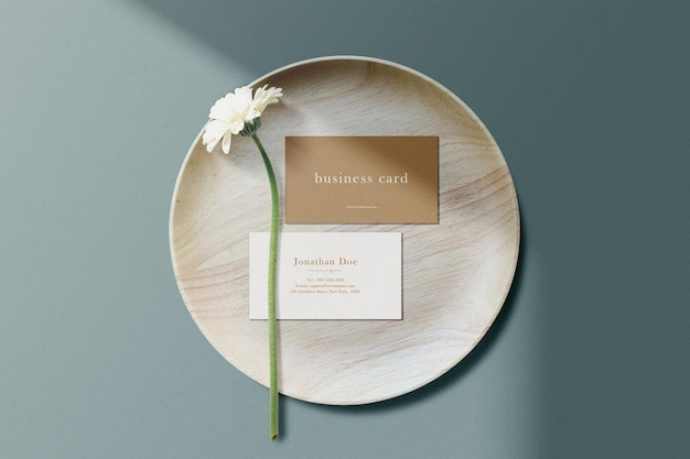 Clean minimal business card mockup on wooden plate with flower