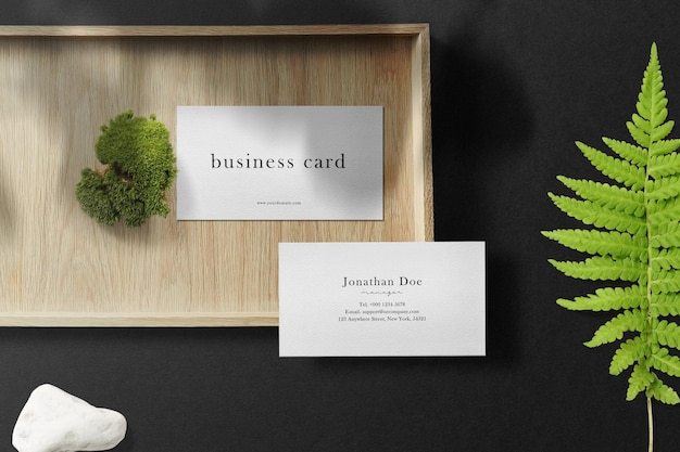 Clean minimal business card mockup on wooden plate with green moss.
