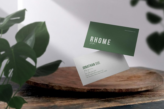 Clean minimal business card mockup on wooden plate with leaves