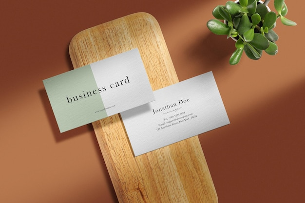 Clean minimal business card mockup on wooden plate with plant