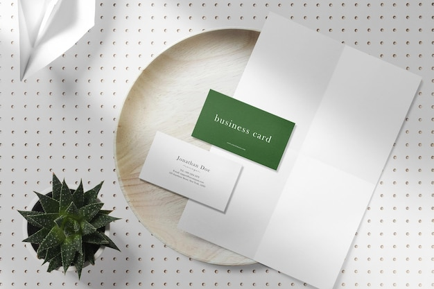 Clean minimal business card and white paper mockup on wooden plate with plant